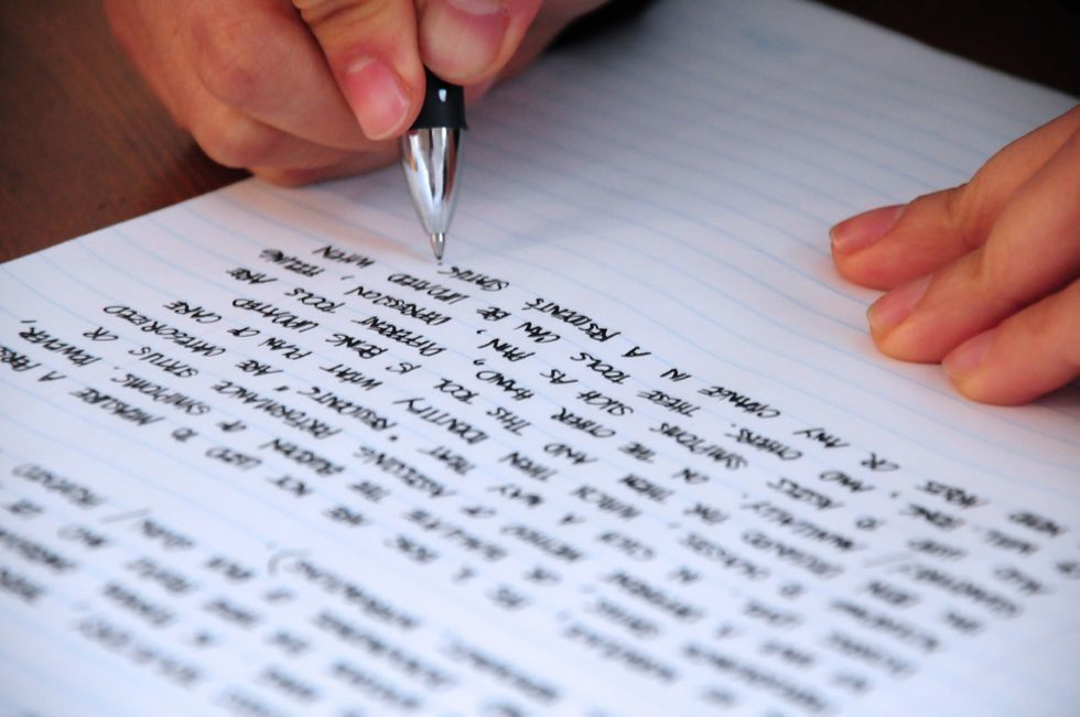 writing on a page with a hand holding a pen as if the person is beginning to write something