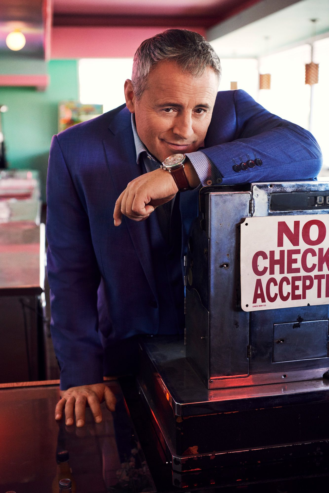 Matt LeBlanc at a vintage cash register looking into the camera wearing a blue suit.