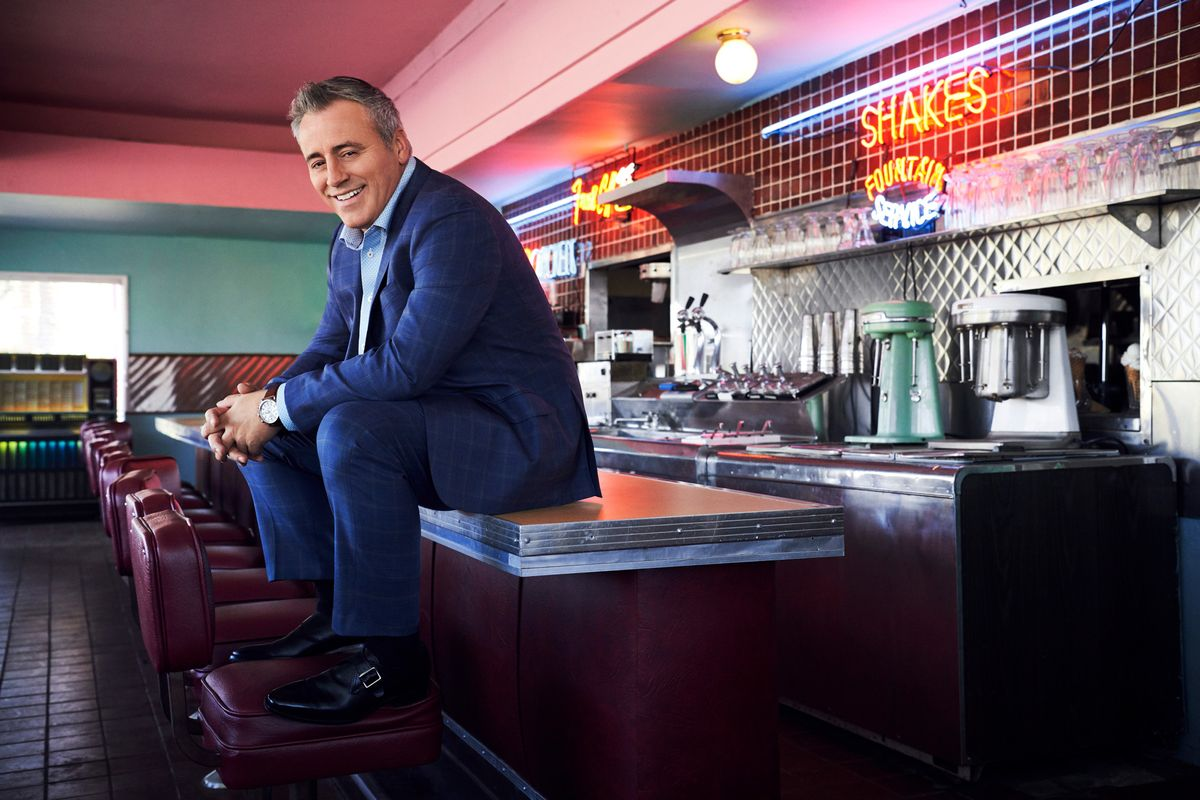 Matt LeBlanc in a vintage diner sitting on the counter with his feet on the seat.