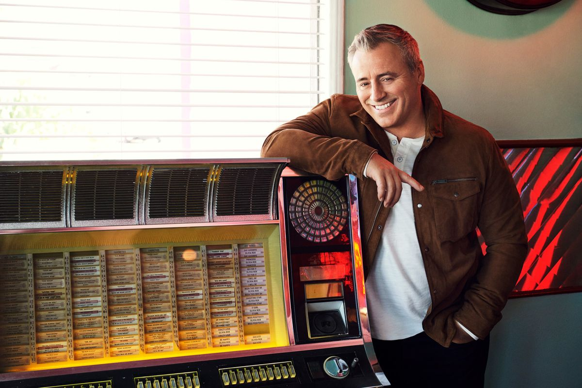 Matt LeBlanc standing at a vintage juke box wearing a brown suede jacket.