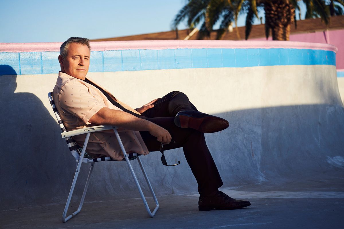 Matt LeBlanc sitting in an empty swimming pool wearing a vintage short-sleeve collar shirt.