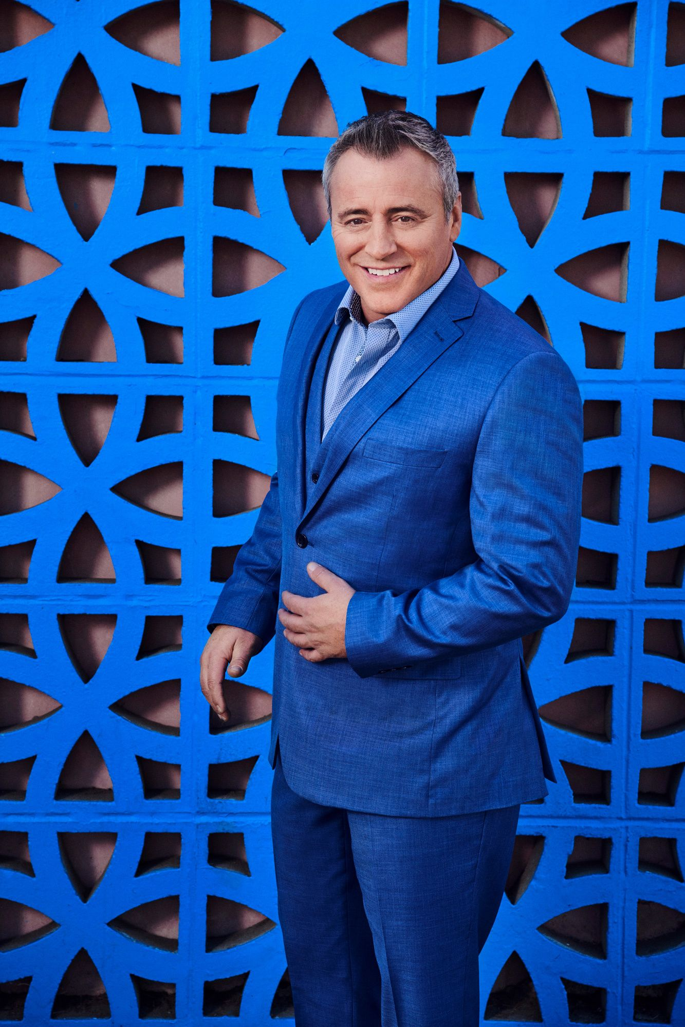 Actor Matt LeBlanc standing in front of a bright blue ornate deco wall wearing a blue suit .