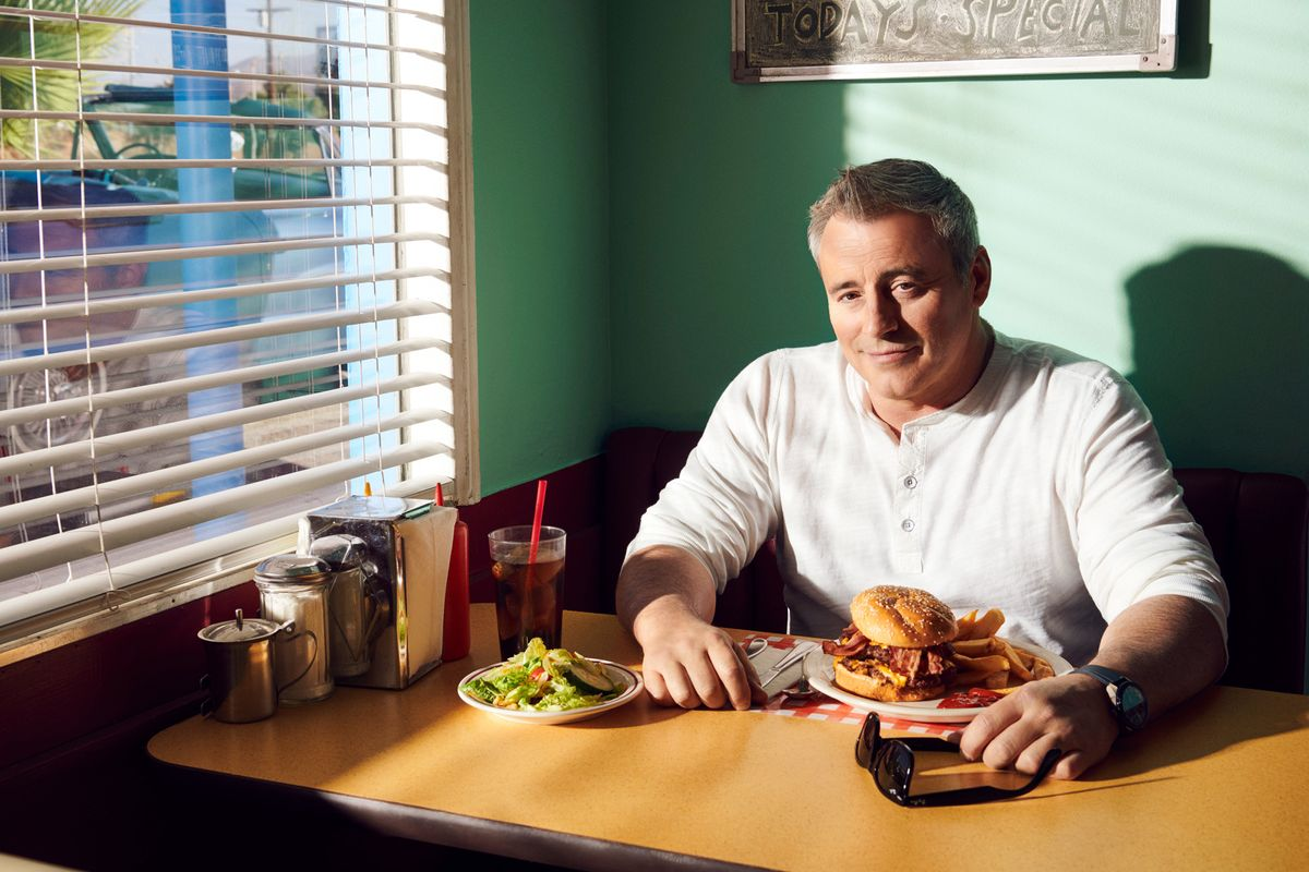 Matt LeBlanc sitting in a booth at a vintage diner with a burner and fries.