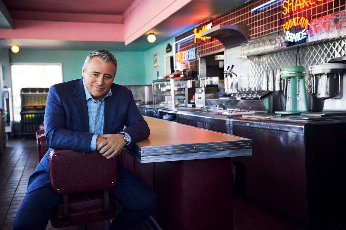 Matt LeBlanc sitting astride on a stool at the counter in a vintage diner smiling into the camera.