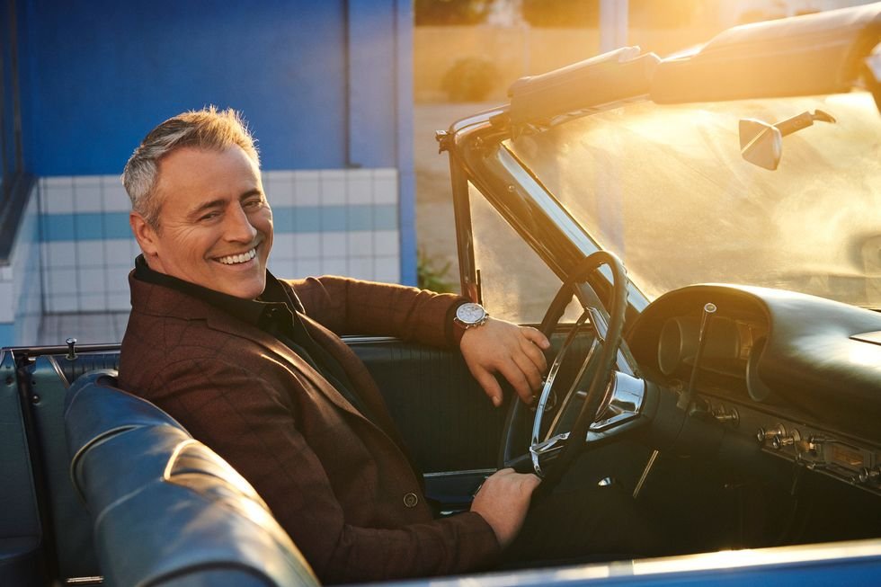 Matt LeBlanc sitting in a vintage Ford convertible smiling.