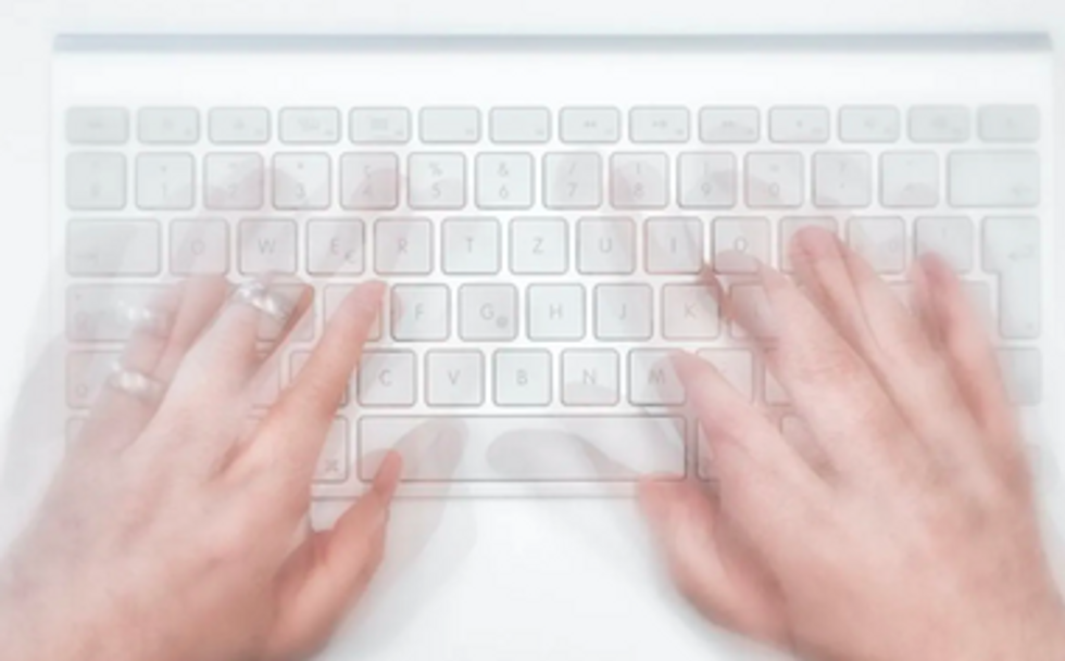 Hands typing on a white laptop