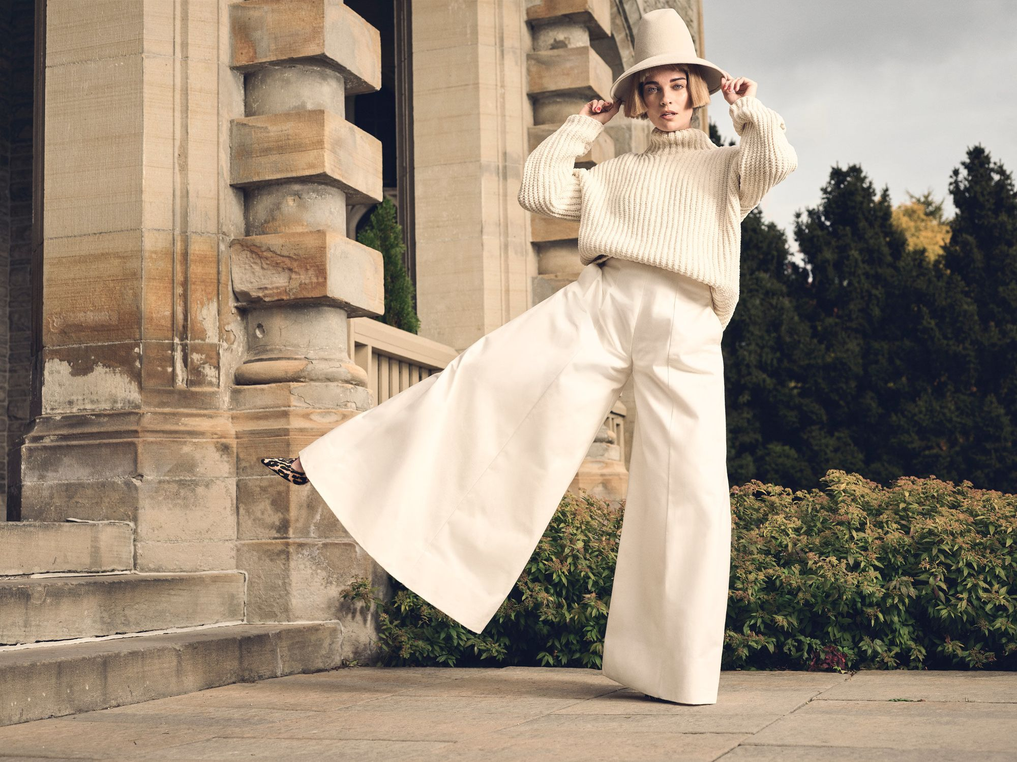 Annie Murphy wearing all white and extra-wide pants.