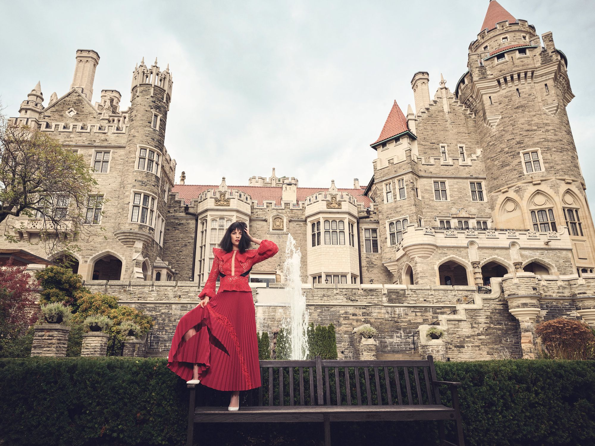 Annie Murphy in red in front of a castle.