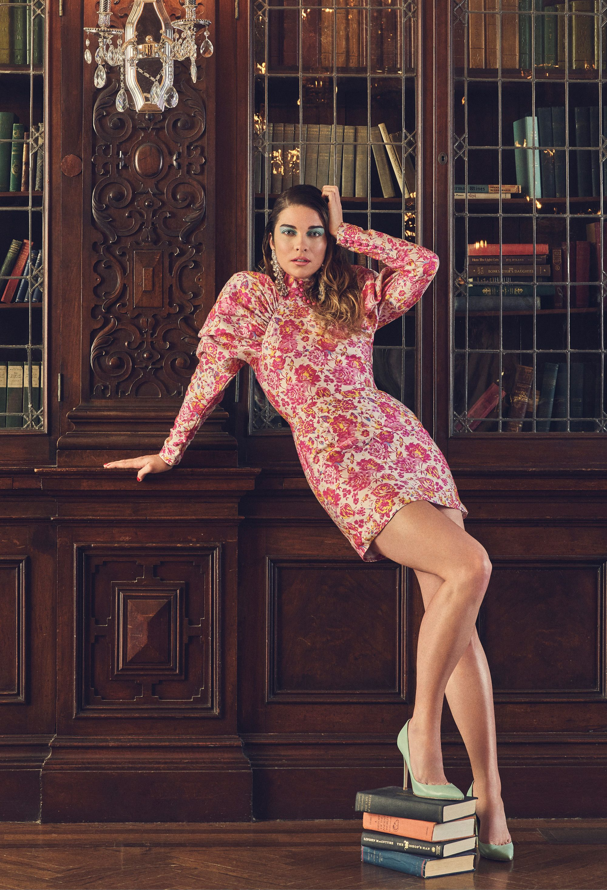 Annie Murphy in a floral dress in front of a vintage bookcase.