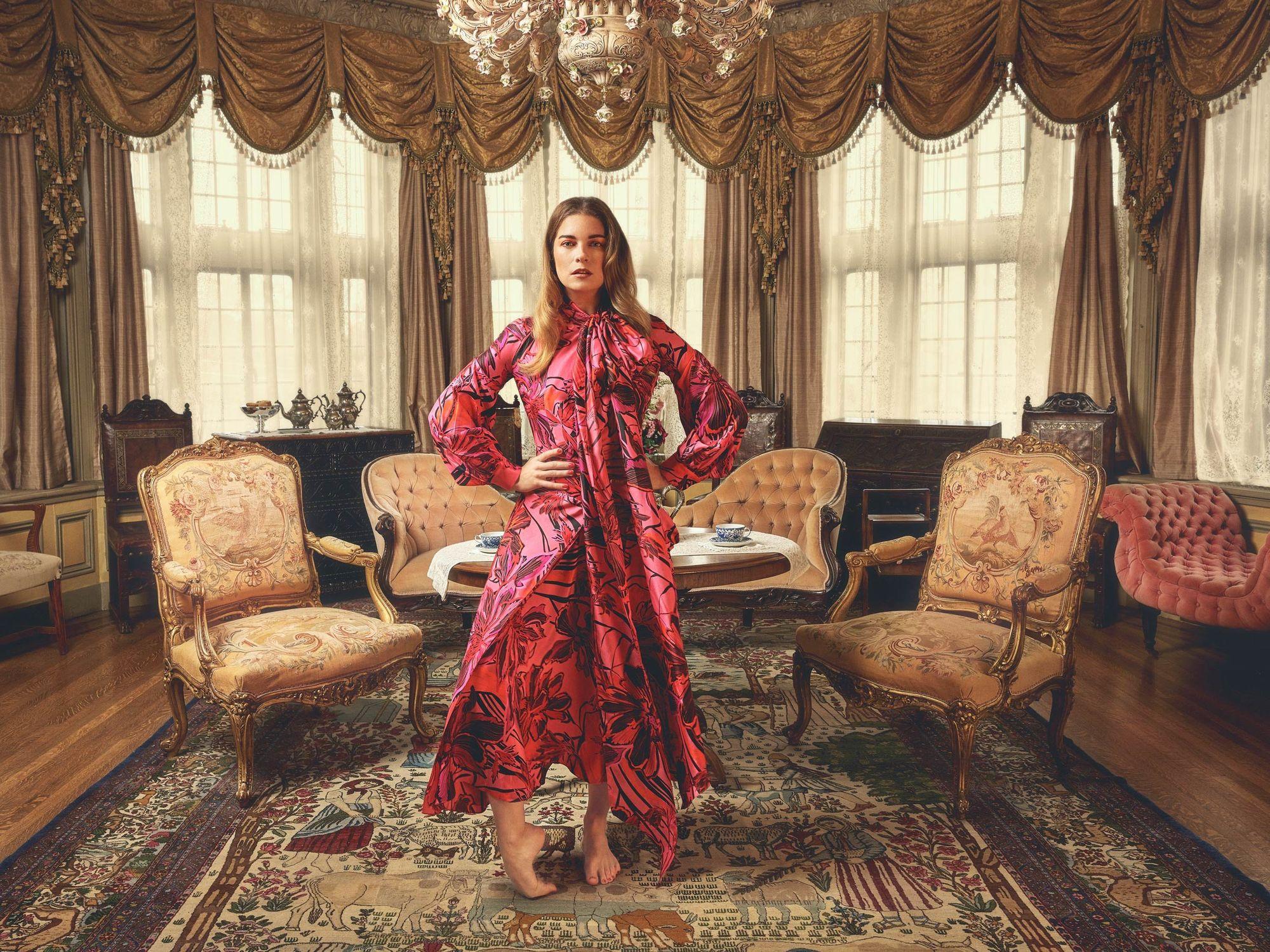 Annie Murphy standing in an elegant sitting room.