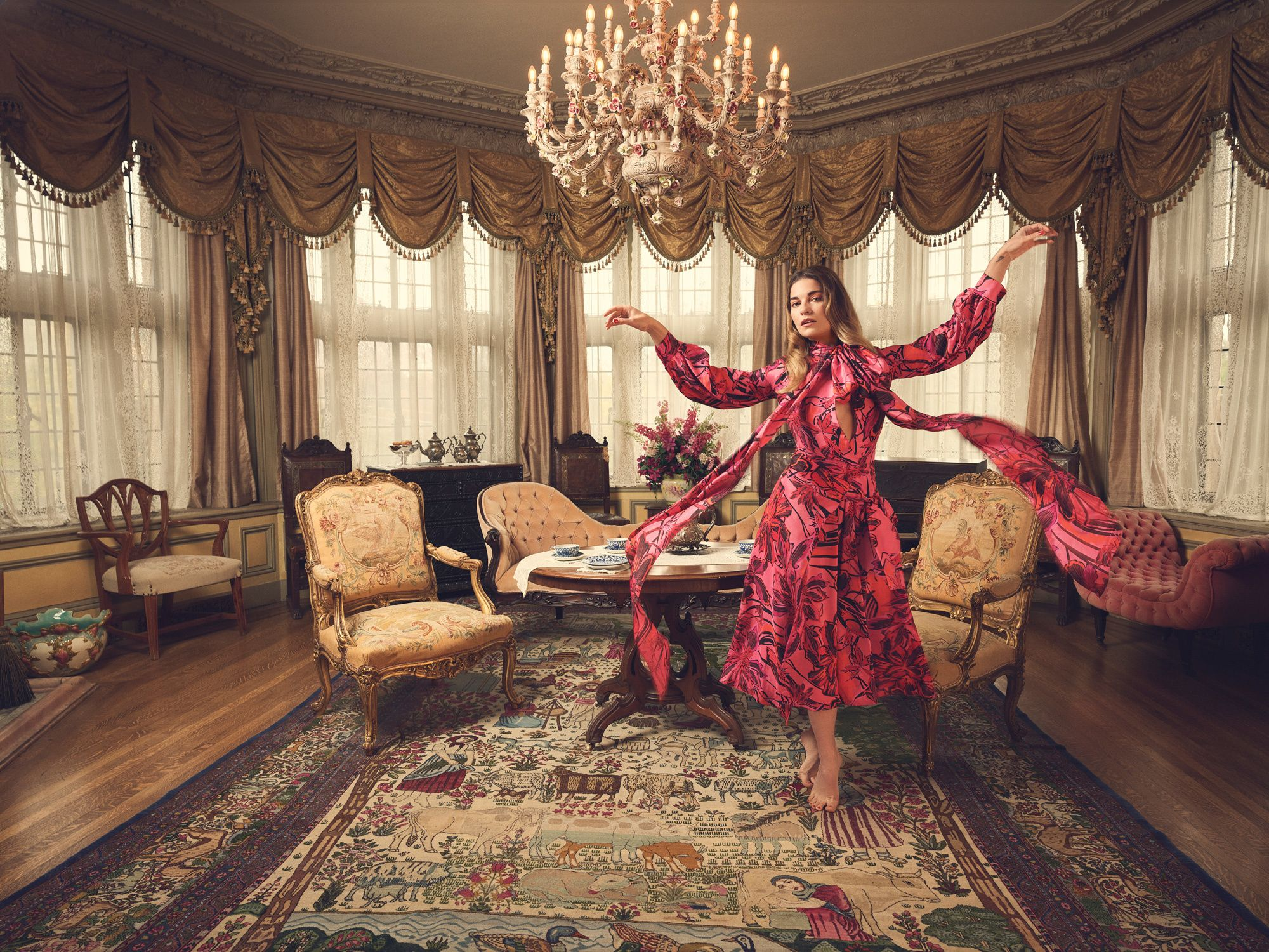 Annie Murphy twirling in an elegant sitting room.