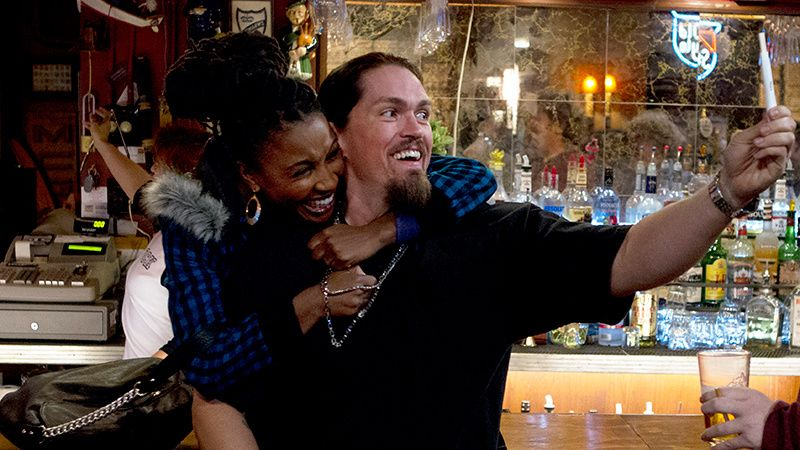 Actors Shanola Hampton and Steve Howey in a bar.
