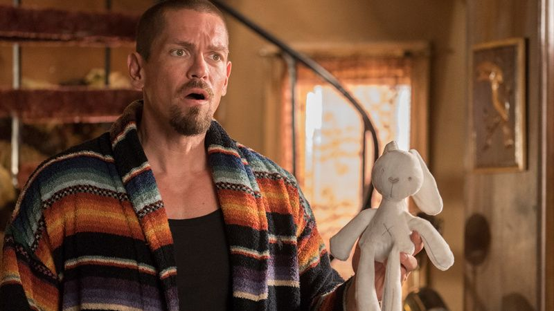 Steve Howey holding a stuffed animal bunny toy.
