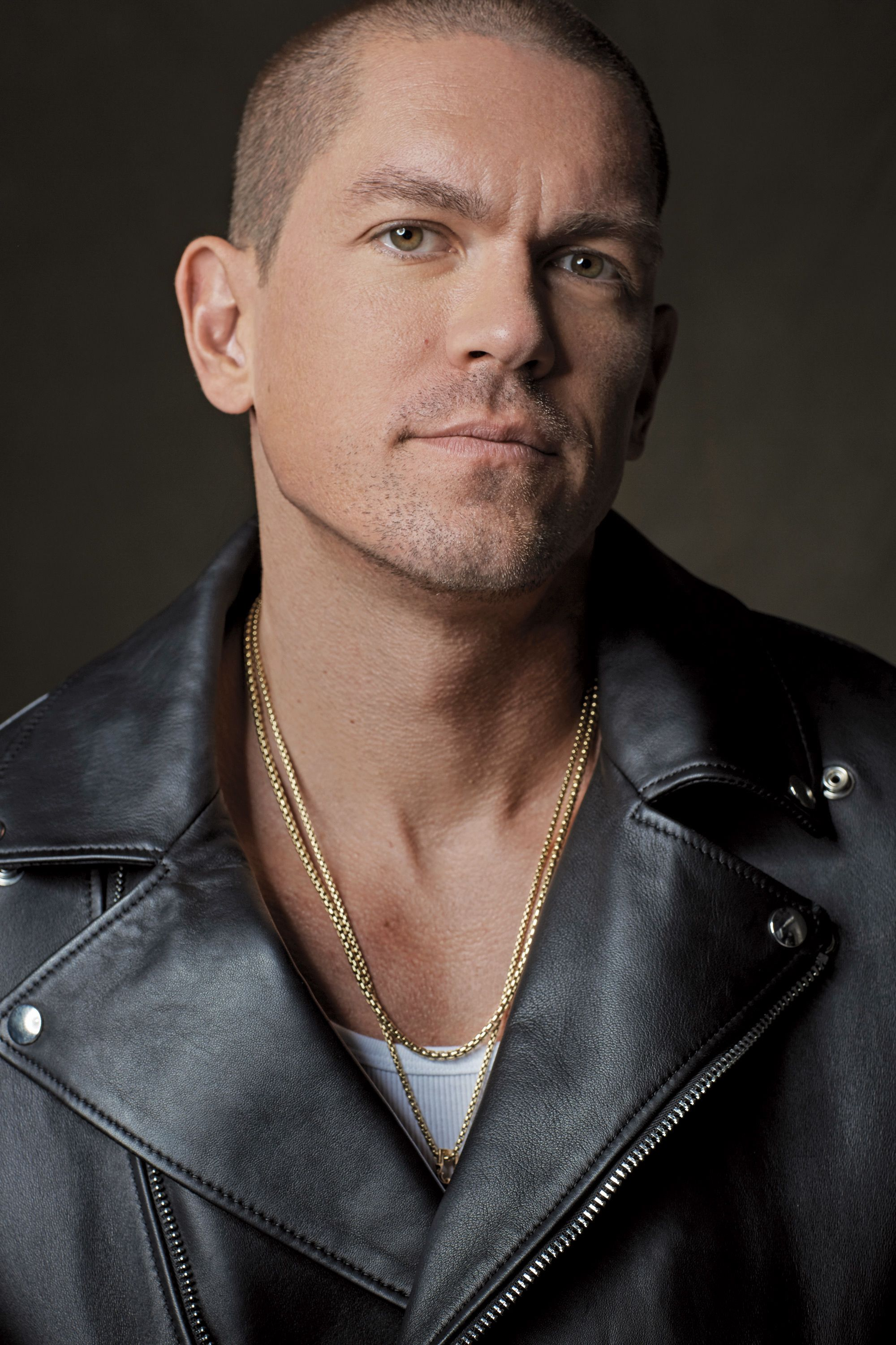 Actor Steve Howey in a leather motorcycle jacket.