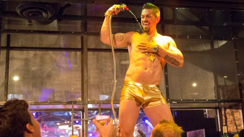 Steve Howey in gold short shorts dancing sexy on a bar.