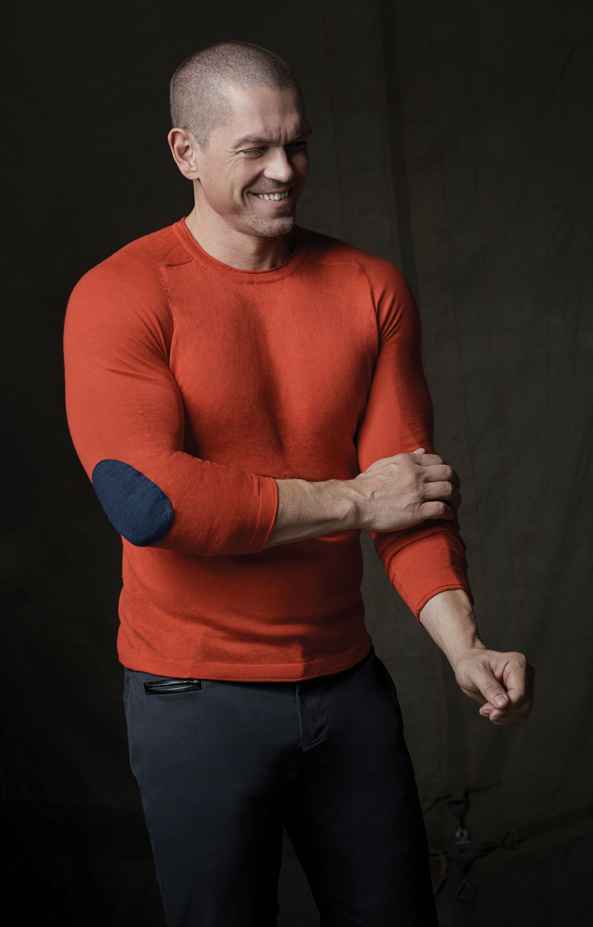 Actor Steve Howey laughing and wearing an orange sweater.