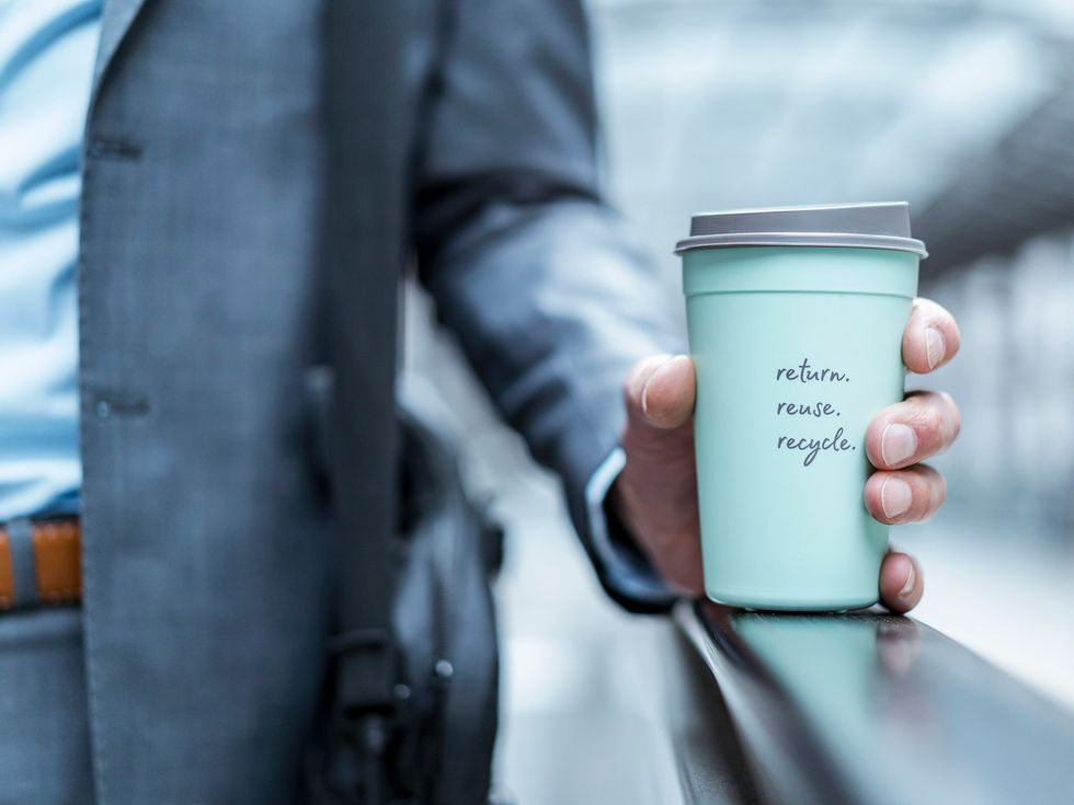 Close-up of businessman holding recycable takeaway coffee cup