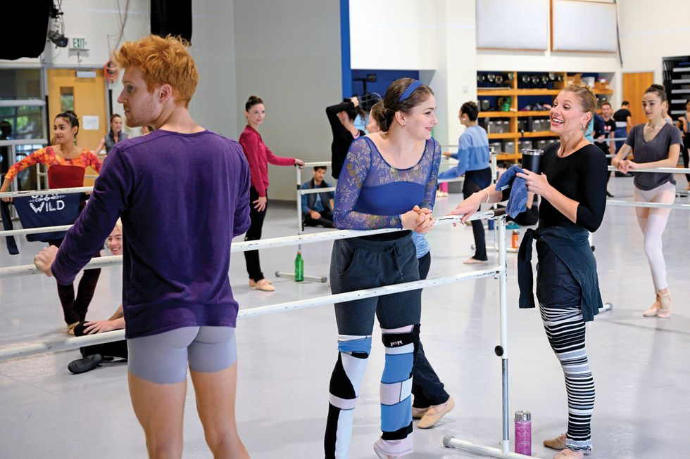 Morgan stands with a group of dancers at the barre before class. She smiles and leans on the barre as another dancer is talking.