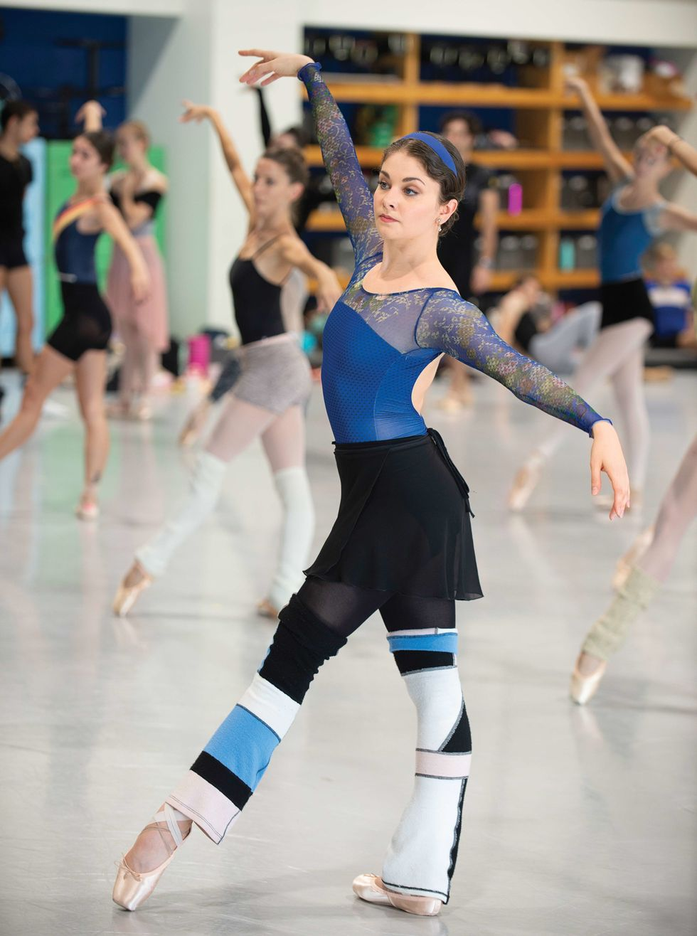 Morgan, in a blue leotard, black tights and skirt and color blocked legwarmers stands in a tendu front in class, with a serious expression on her face.