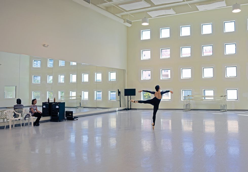 Morgan is seen from behind in an arabesque on pointe. Lopez sits in a white plastic chair in front of the mirror, watching her.