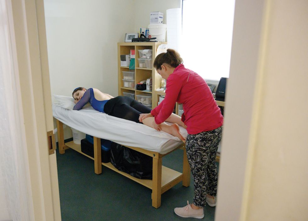 Morgan lies face down on a massage table. A body worker in a red top and patterned pants stands behind her, working on her calf.