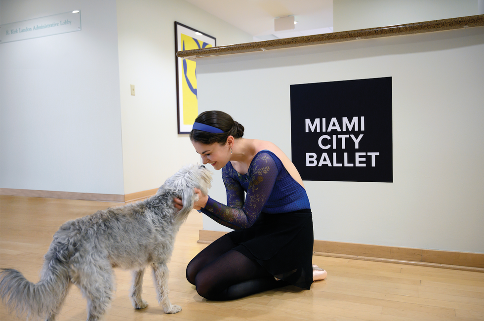 Morgan kneels on the floor with her hands on a scruffy gray dog. Behind her is a counter with the words Miami City Ballet printed.
