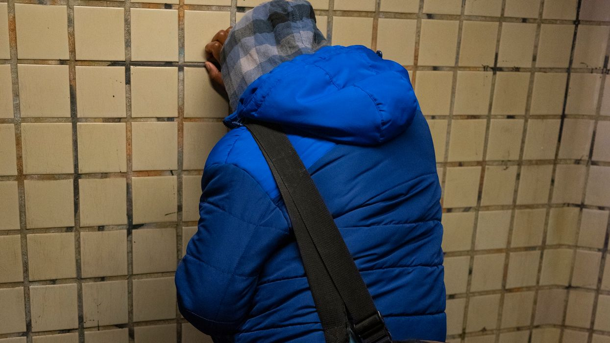 Man leaning against a wall in the New York City subway