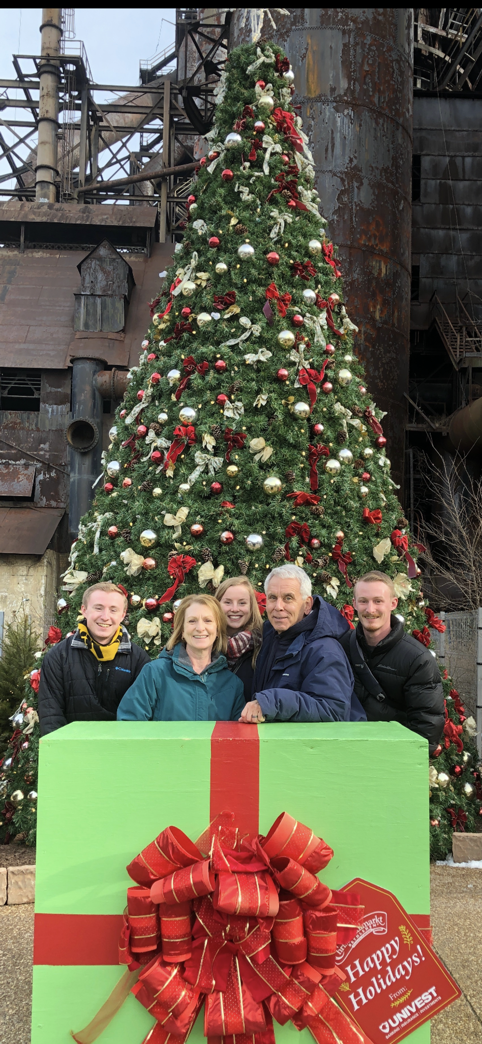 Colin Romaglia (left) stands in front of a Christmas Tree with his family in Pennsylvania.