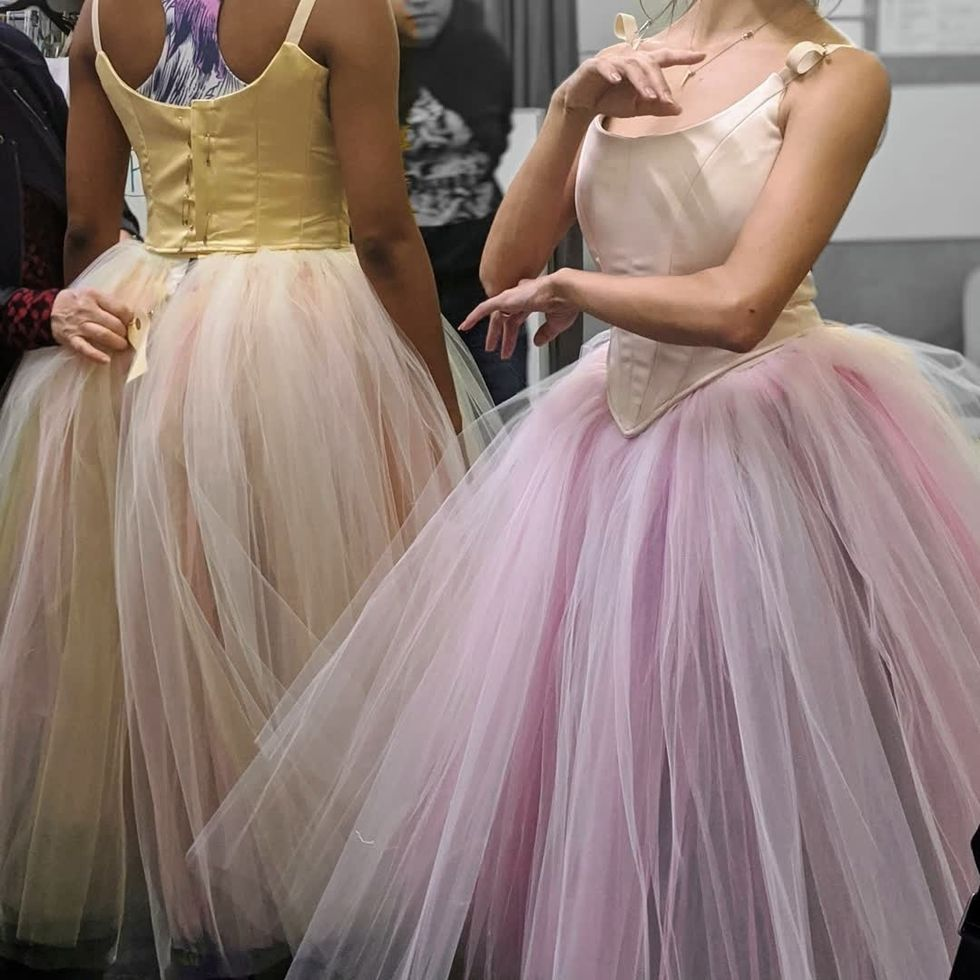The torsos of two dancers, one in a yellow tutu and one in light pink, which still have pins in the back.