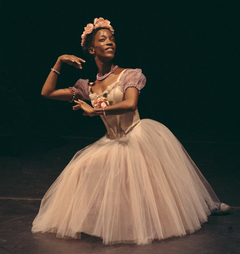 Jones, dressed in a very pale pink tutu costume, poses on the ground with her arms framing her face.