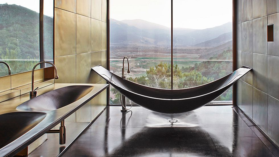 An exotic bathtub with a view of verdant hills
