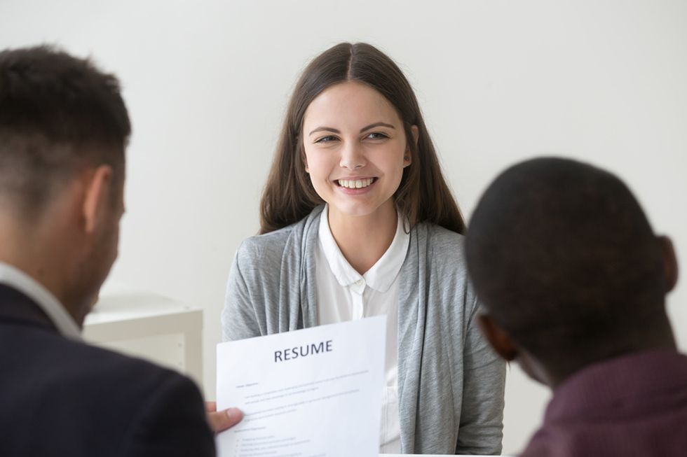 Job seeker smiles as two hiring managers read her well-written resume