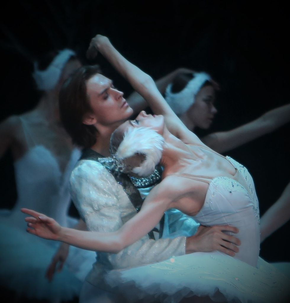 Kolesnikova, dressed in a white Odette costume leans back against Rodkin with her arms in the air.