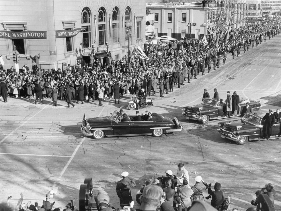 President John F Kennedy is driven through the crowded streets with his wife Jackie on the day of his inauguration. (