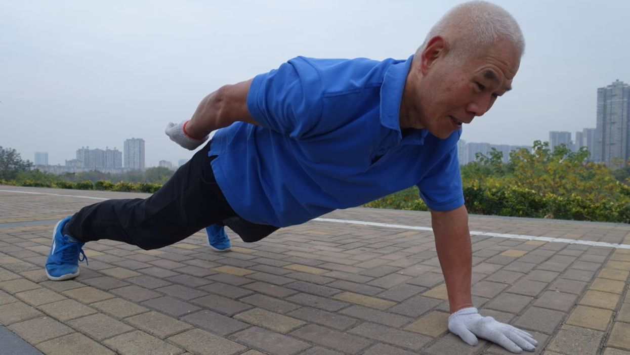 Elderly man doing a one-handed pushup
