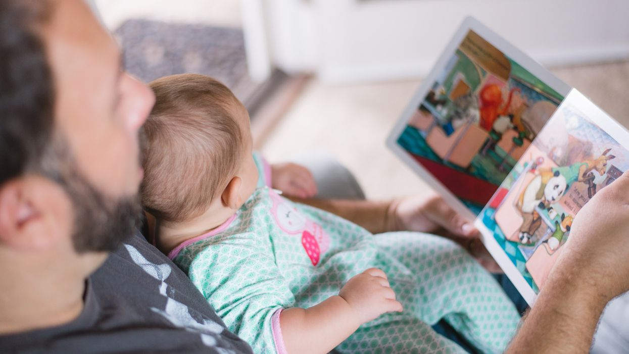 father reading a book to a baby