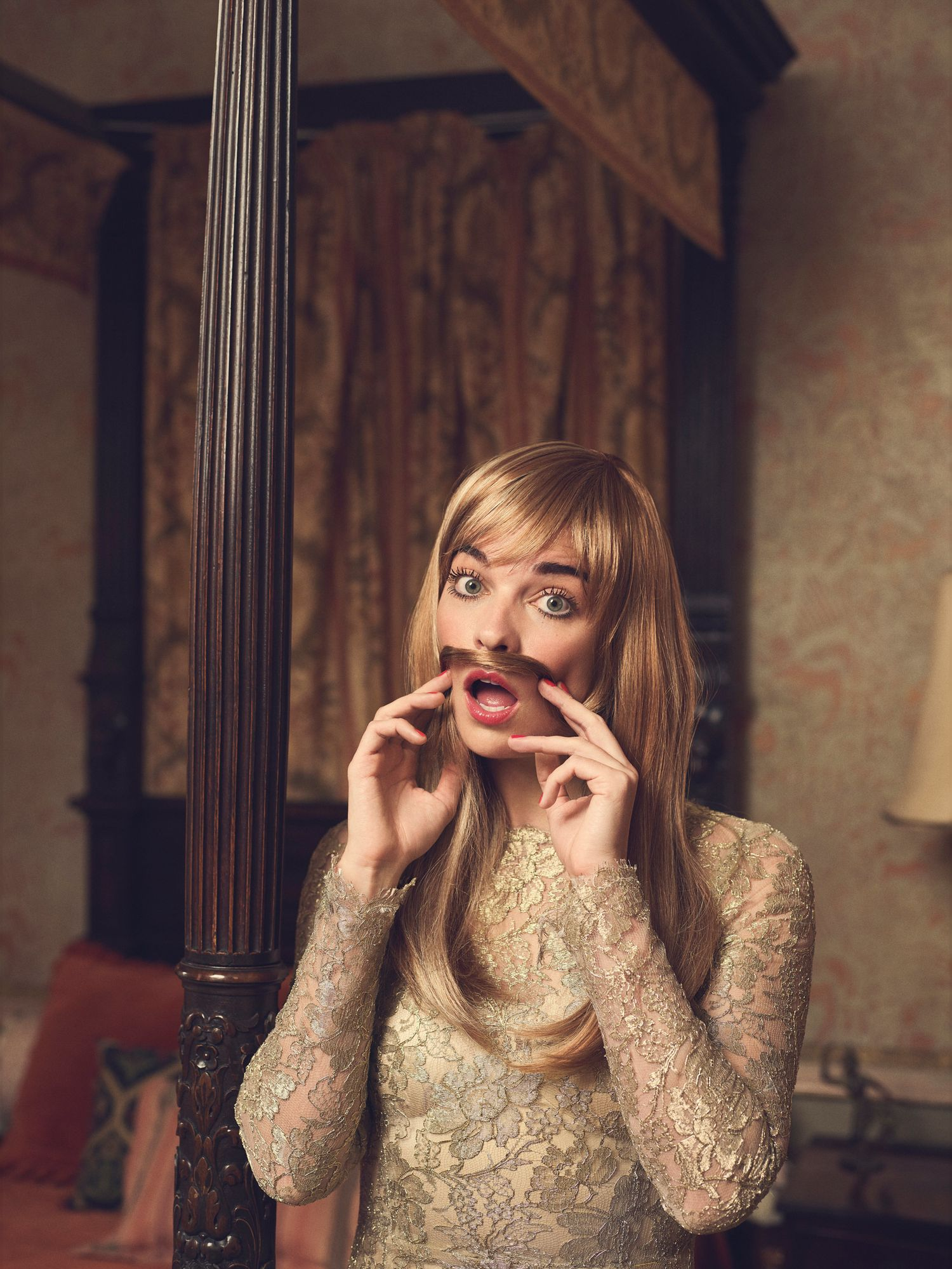 Annie Murphy in a gold dress, making a fake mustache with her hair.