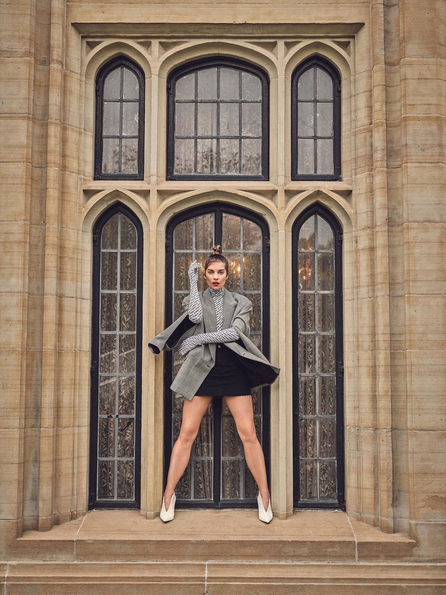 Annie Murphy standing in front of ornate window in a short black skirt.