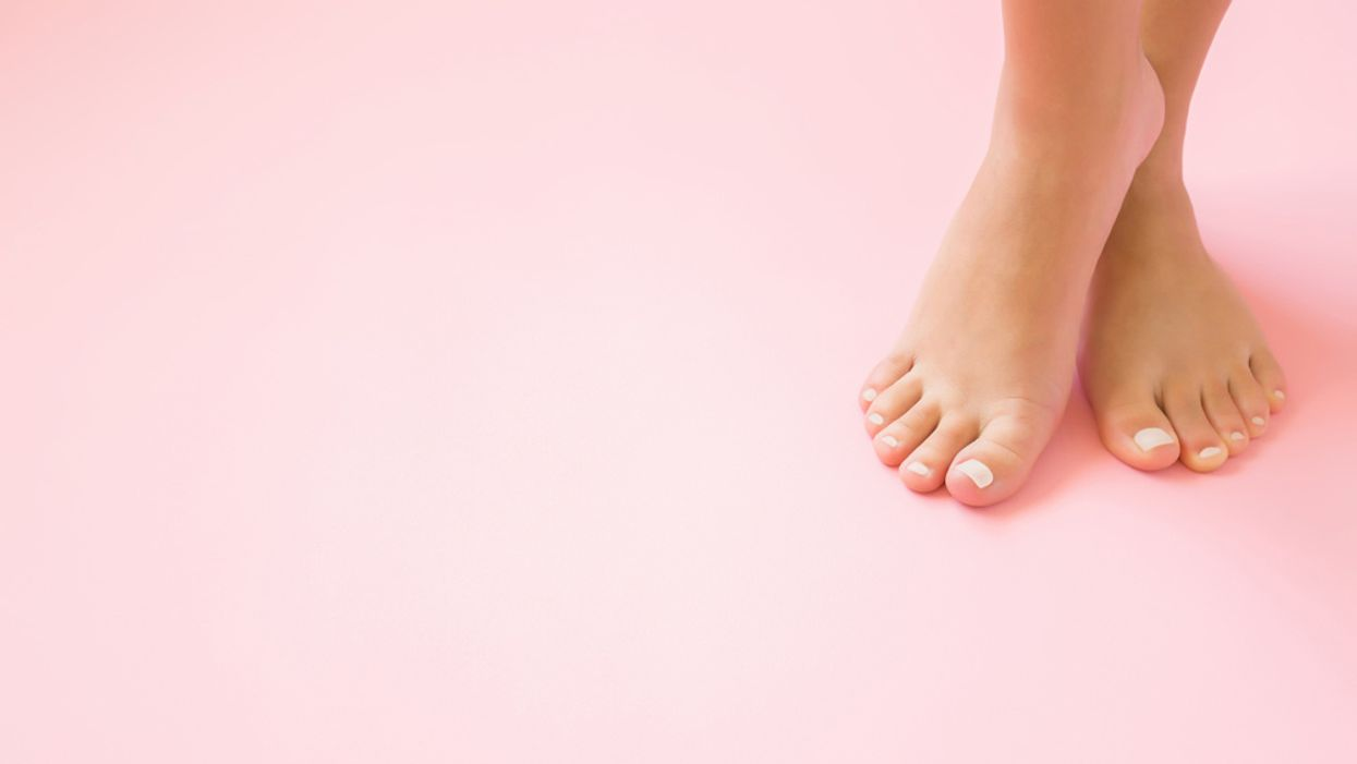 close up of woman's feet on blank pink background