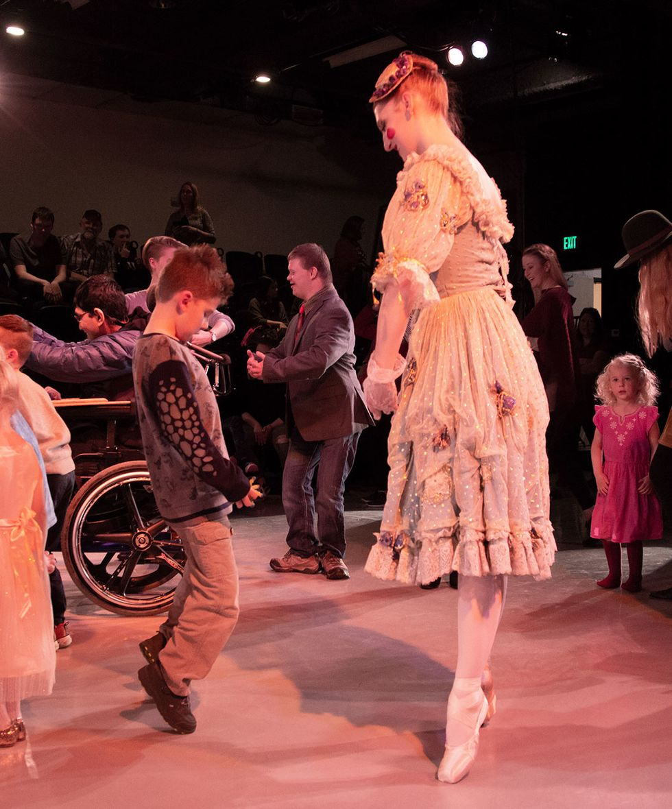 A ballerina demonstrates standing on relev\u00e9 to a young boy. They're surrounding by other children and adults practicing dance moves.