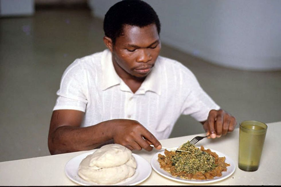 Man eating egusi soup and pounded yam