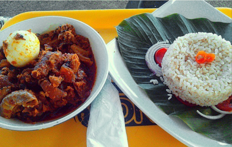Nigerian Ofada stew with rice and banana leaf and egg.