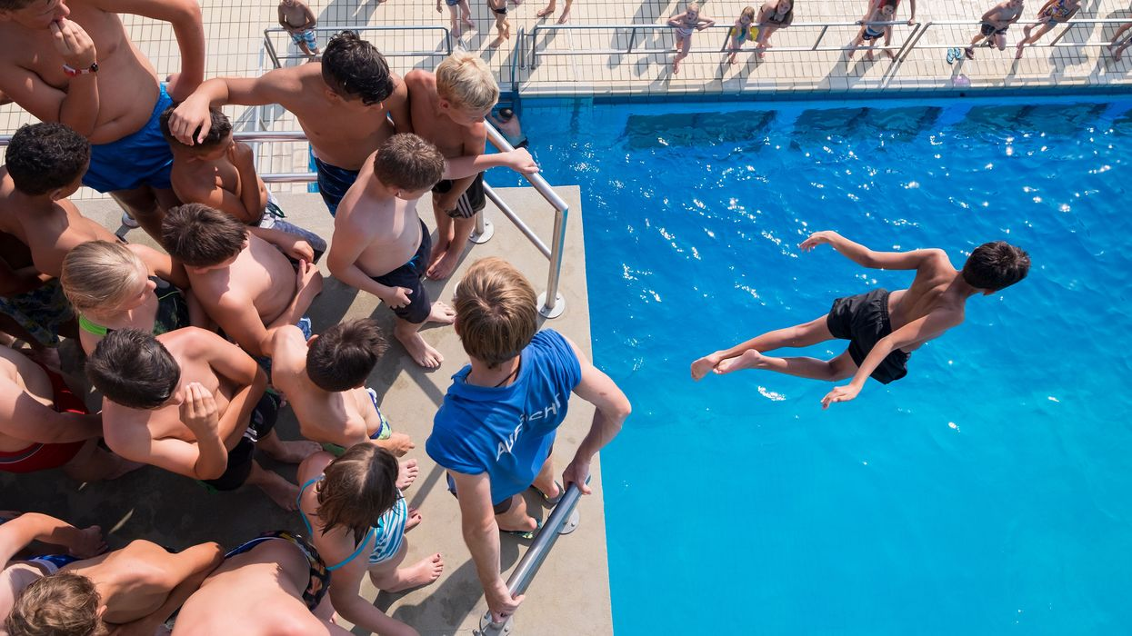kids jumping into a large swimming pool