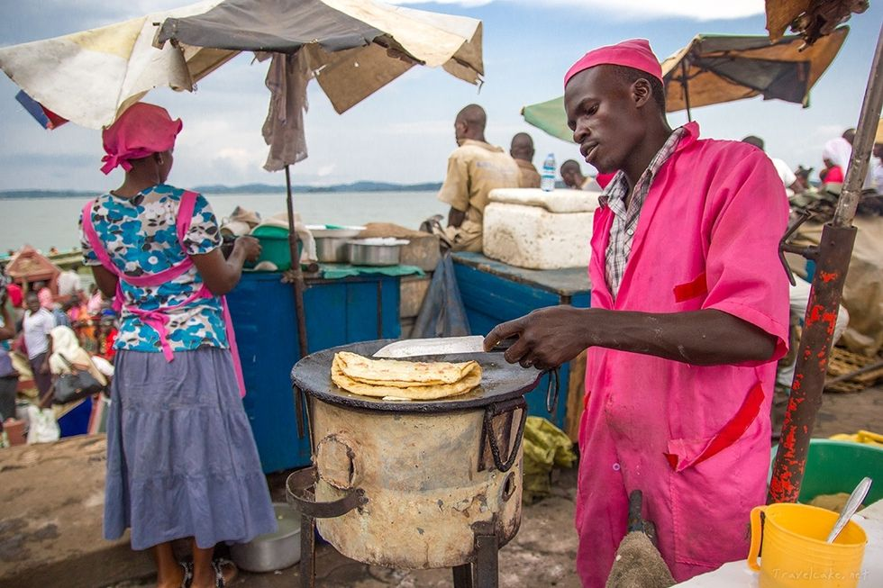"""The image shows a """"Rolex"""" merchant frying chapatis. Rolex in Uganda refers to a delicacy prepared in a few minutes , its made by frying eggs and then a chapati is wrapped around the egg and rolled. It is a very delicious treat, that has gained massive popularity over the years."""