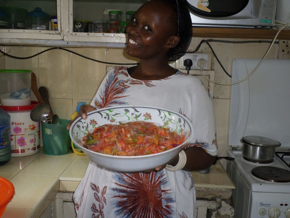 East African woman proudly holds a bowl of Kachumbari. Kiswahili: Mixed Spicy Salad