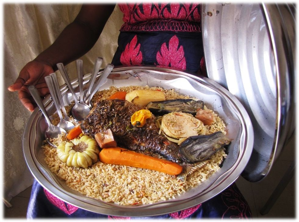 Woman serving Thieboudienne with fish, carrot and aubergine.