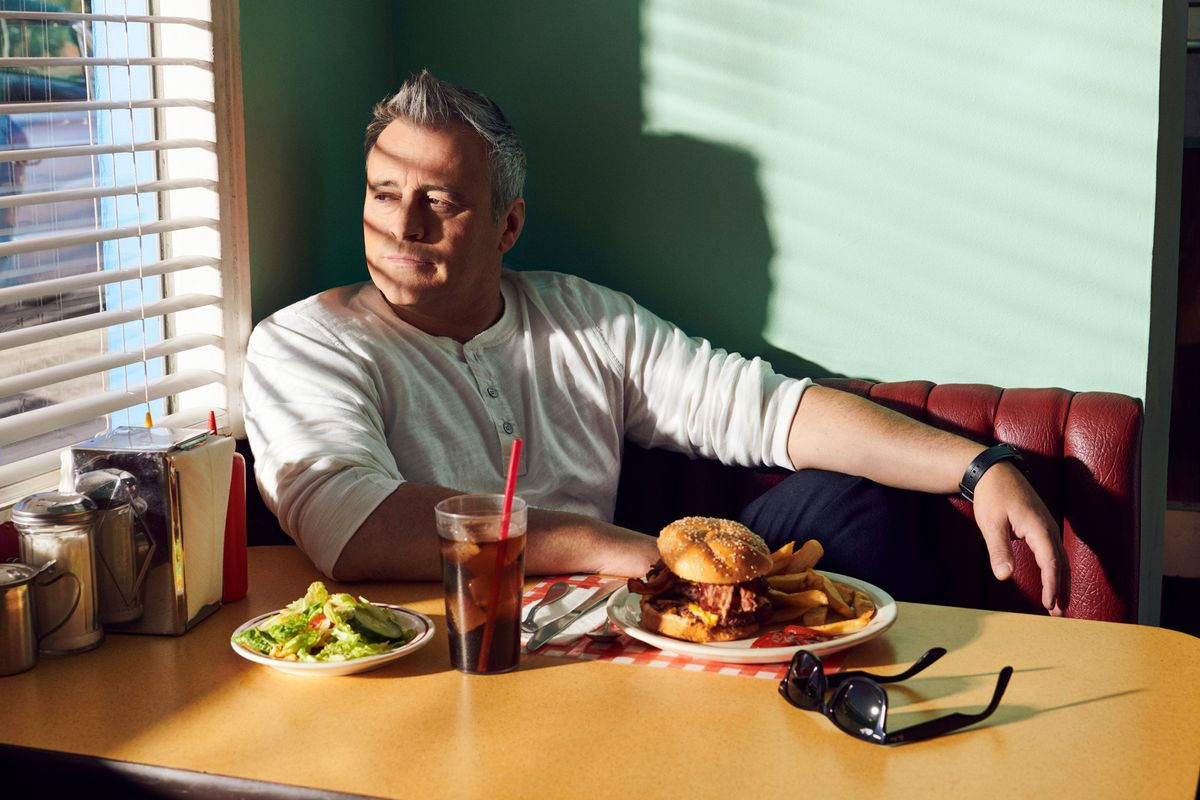 Matt LeBlanc sitting in a booth in a vintage diner with a burger and fries looking into a sunlit window.