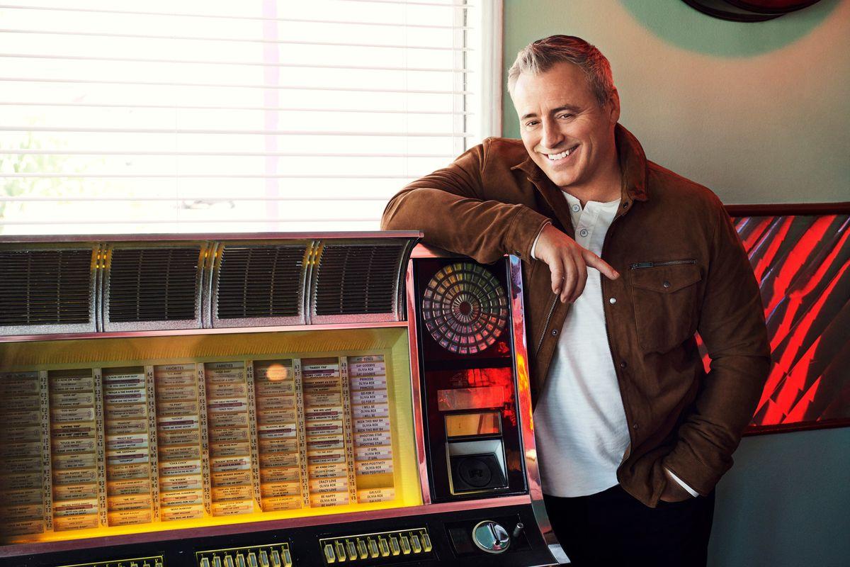 Matt LeBlanc standing at a vintage juke box wearing a brown suede jacket.
