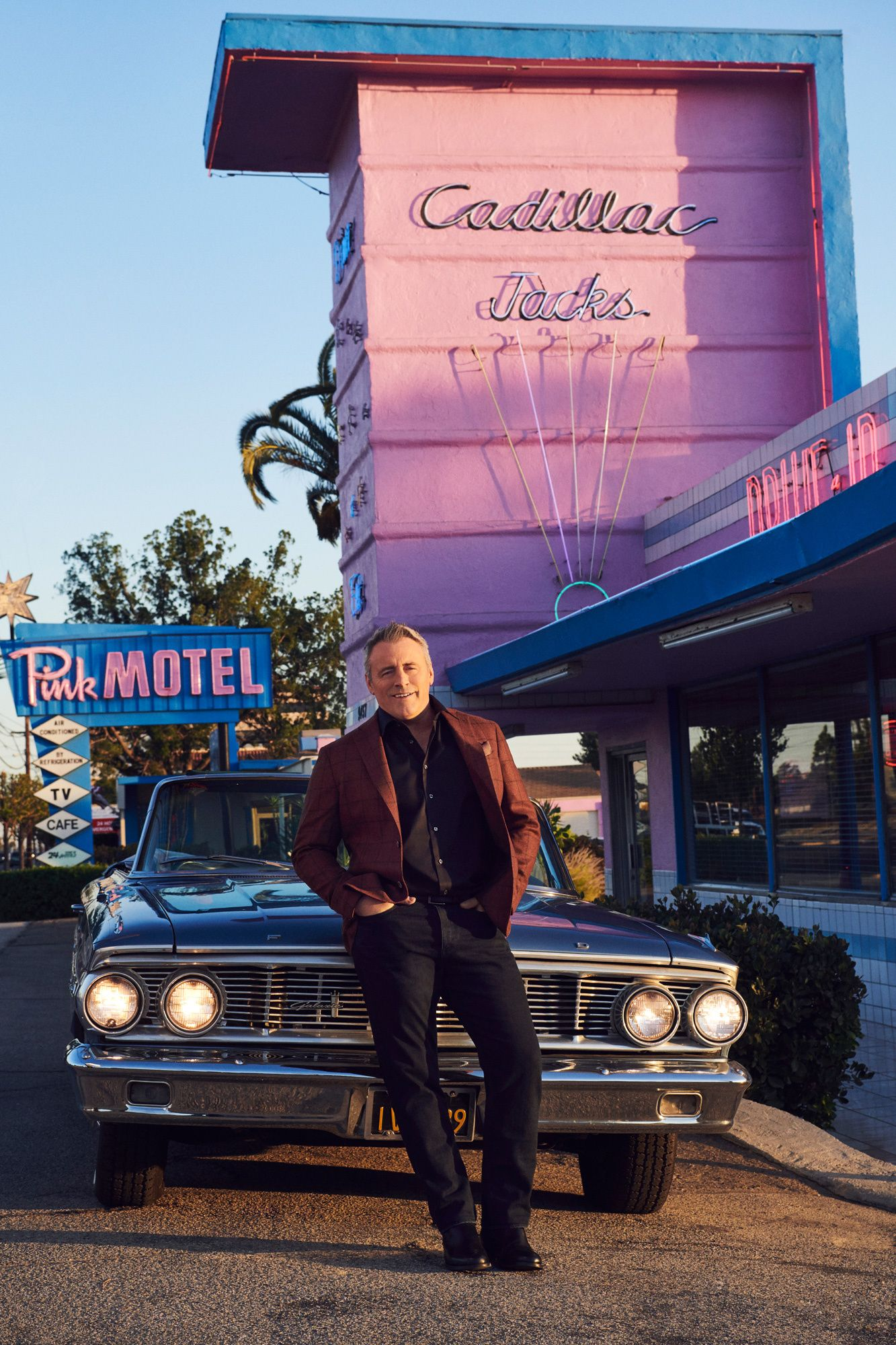 Matt LeBlanc leaning back against a vintage convertible in front of Pink Motel.