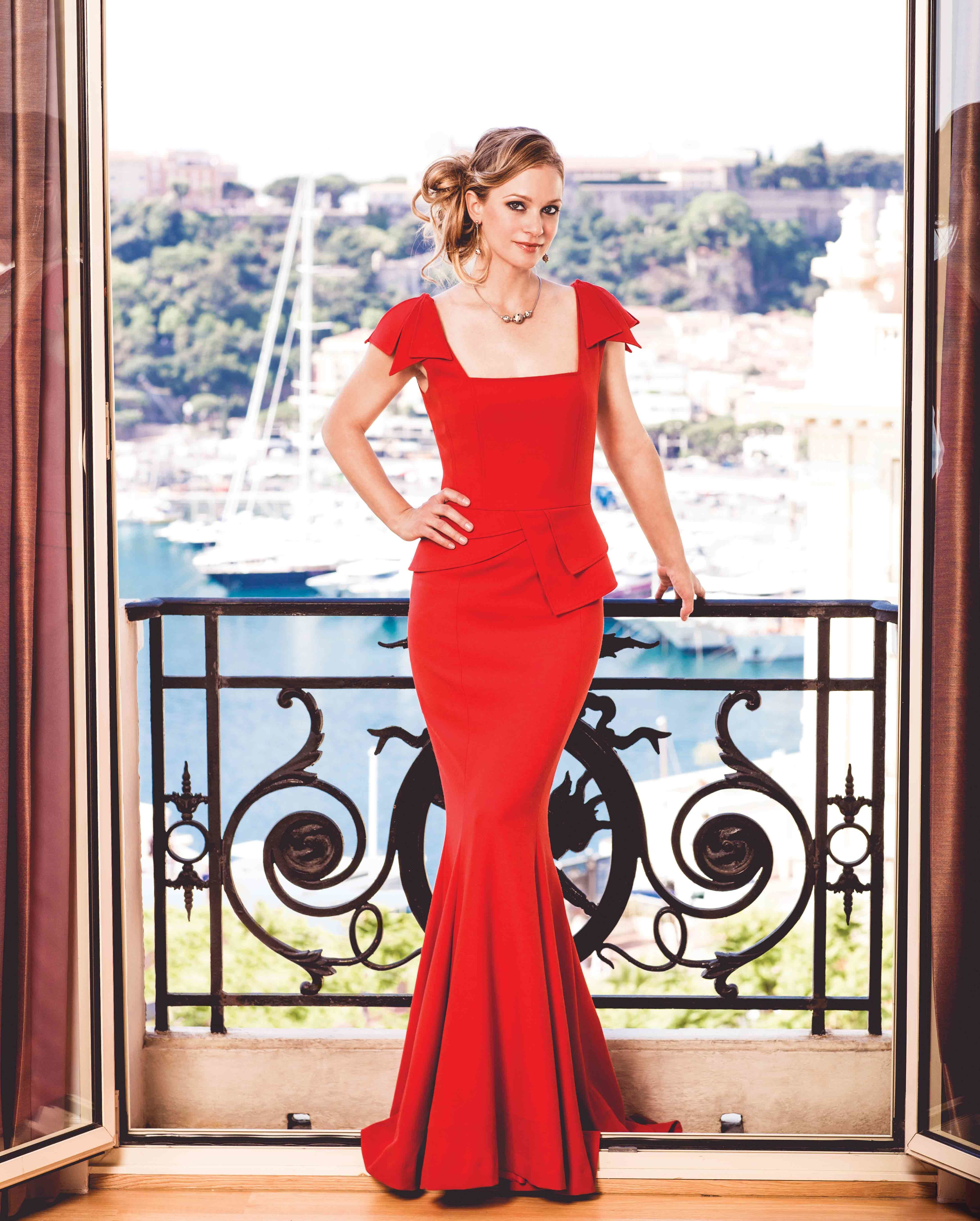 AJ Cook on a terrace in a red dress